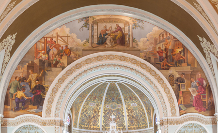 The sanctuary arch of Saint Joseph Church. The Holy Family is pictured at the top of the arch. Steel workers are shown on the left side above priests and John Mallin discussing the decorations. On the right side, a building is shown under construction, while underneath appear Father Henry M. Plaster, who built the church, and Father Jansen, who built the parish school, discussing plans with an architect. Photo credit: Noah Vaughn